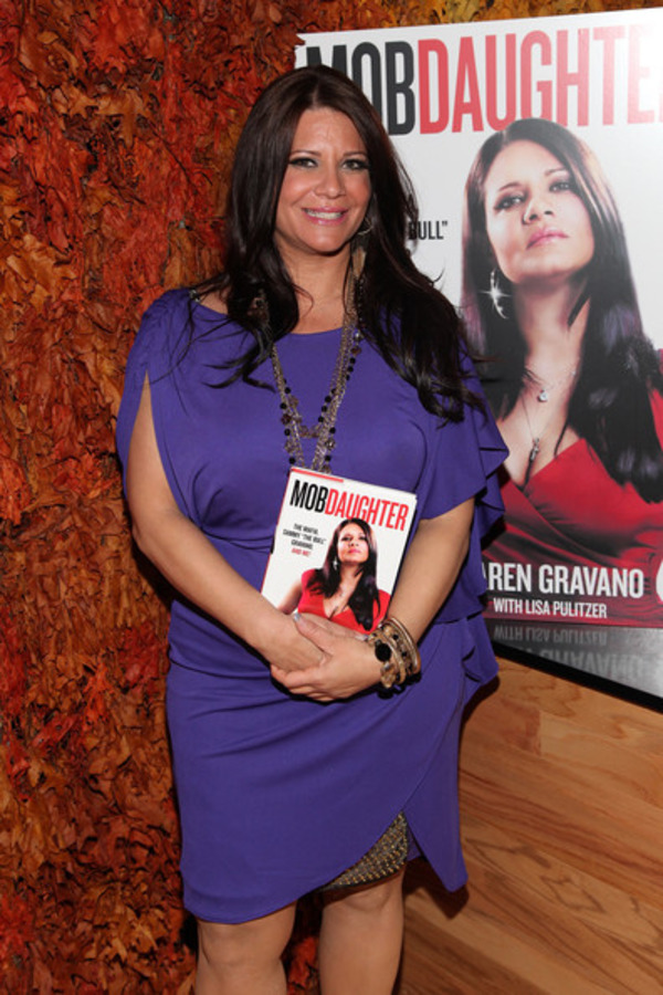 Karen Gravano is posing with her book
